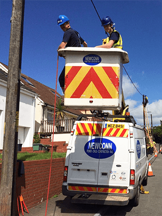 Small image of Newconn workers in cherry picker and newconn vehicle next to a woodpole line.