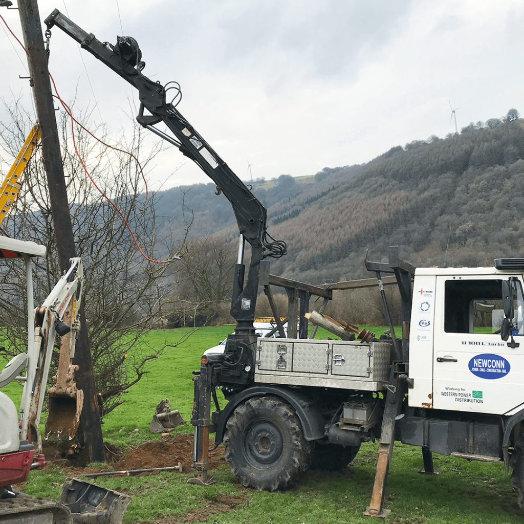 Wooden pole being installed by vehicle and crane on site in wales